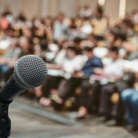 Microphone over the Abstract blurred photo of conference hall or seminar room with attendee background