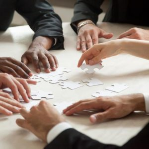 Close up of multiethnic team solving blank puzzle game.
